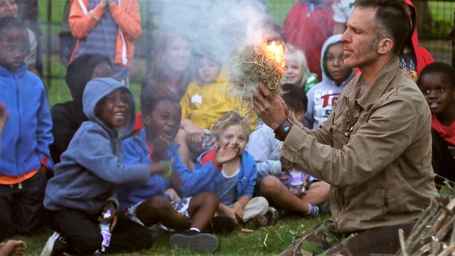 Father Nature - man holding burning hay as part of fire-lighting workshop.