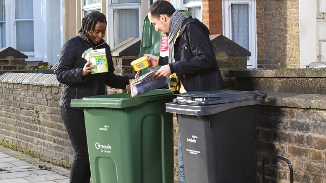 Male and female couple putting recyclable items into a green bin by their front gate.