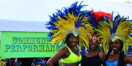 3 women in bright yellow feathewrd headdresses & carnival style costumes smile and pose in front of green 'community' banner at Stockwell Festival
