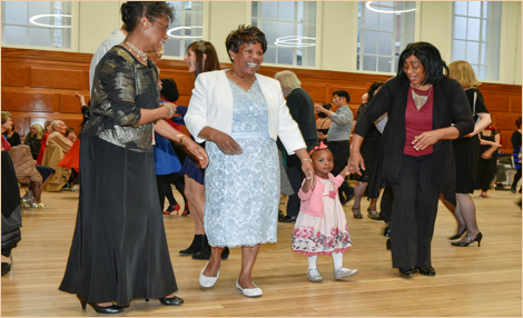Black women dancing with a child