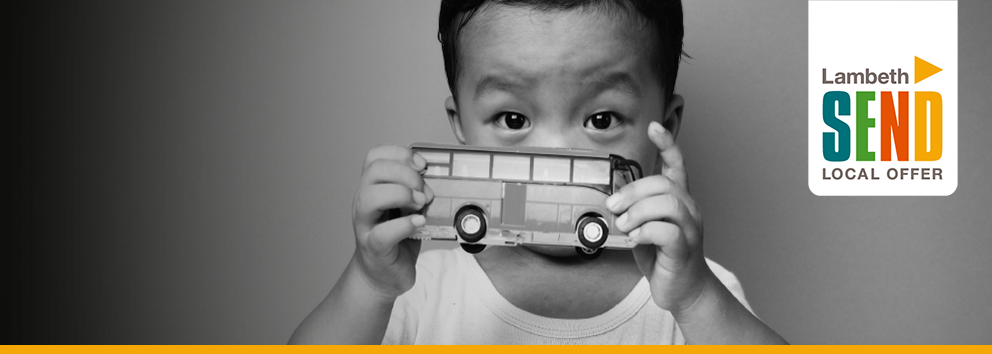 Young male child holding a bus in front of his face, covering his nose and mouth