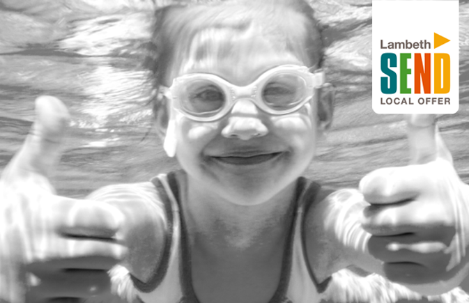 Girl under water in a swimming pool, facing and smiling at the camera with two thumbs up