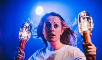 teenage girl holding 2 bulkhead lamps in a scene from play about time travel for young people 'the Forever Machine'
