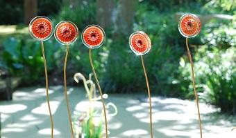 A row of flat glass flowers on stems.