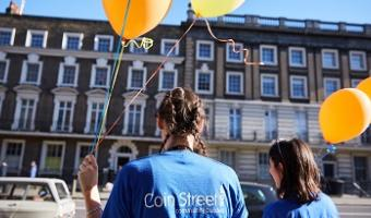 Back view of woman and girl in dark blue Coin Street Community Builders T-shirts holding CSCB orange balloons