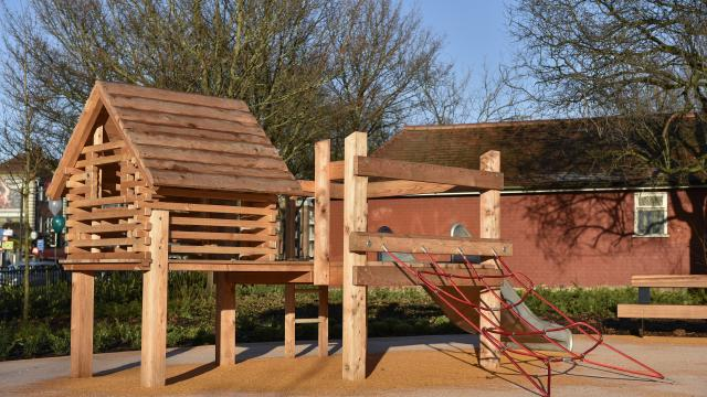 a wooden play house with a slide and rope climbing ladder